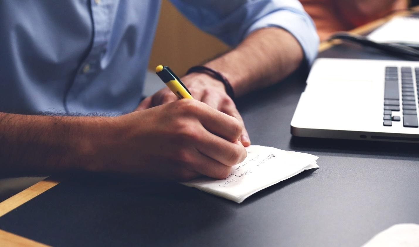 Image of a man's hand writing on a piece of paper.